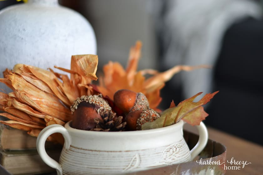 pottery bowl filled with fall leaves, acorns, and pine cones