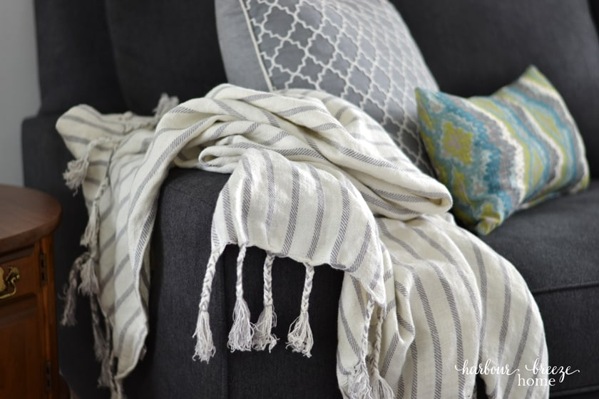 striped linen blanket draped over the arm of a couch