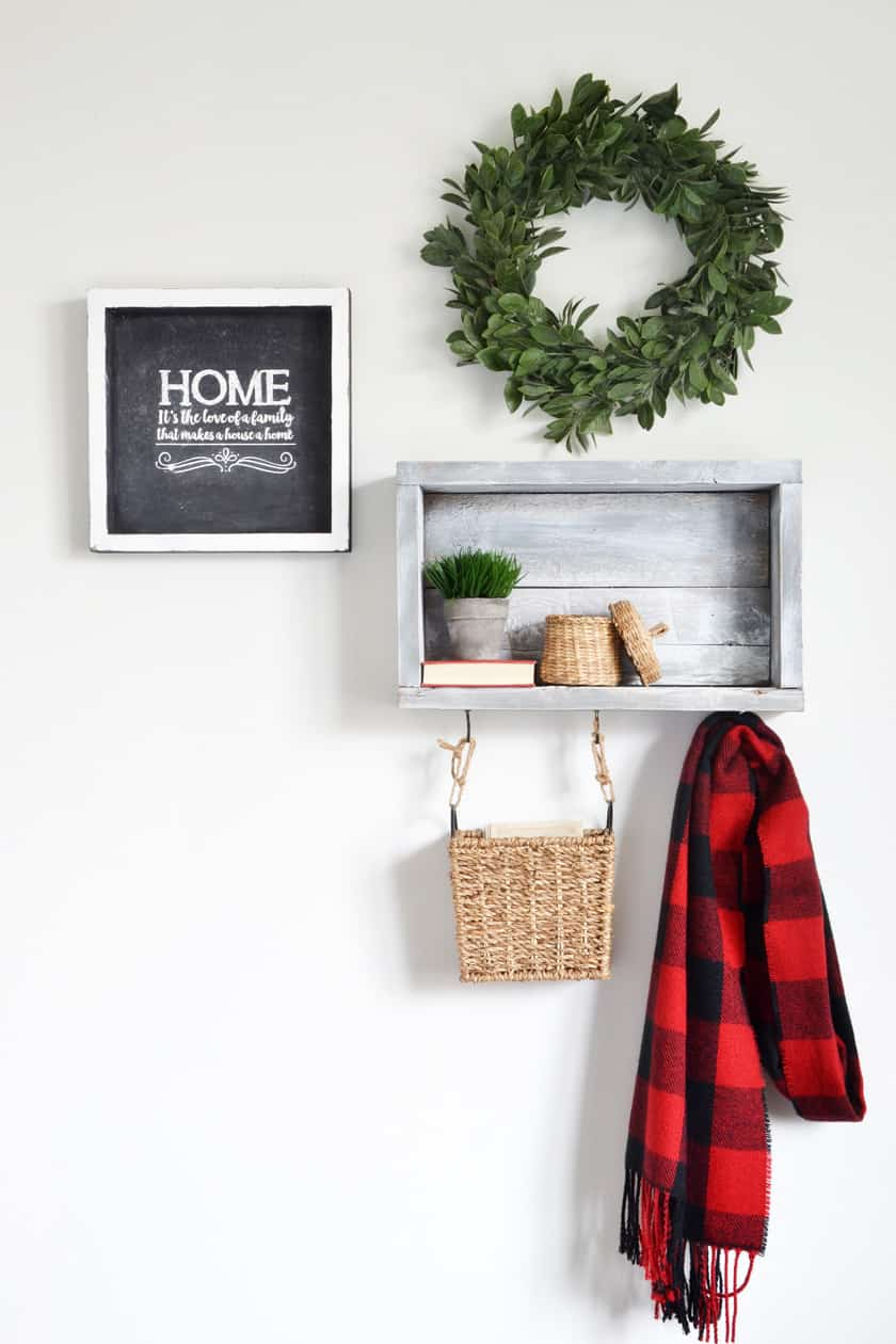 A wooden shelf with hooks for scarves and a basket for keys in the entryway.