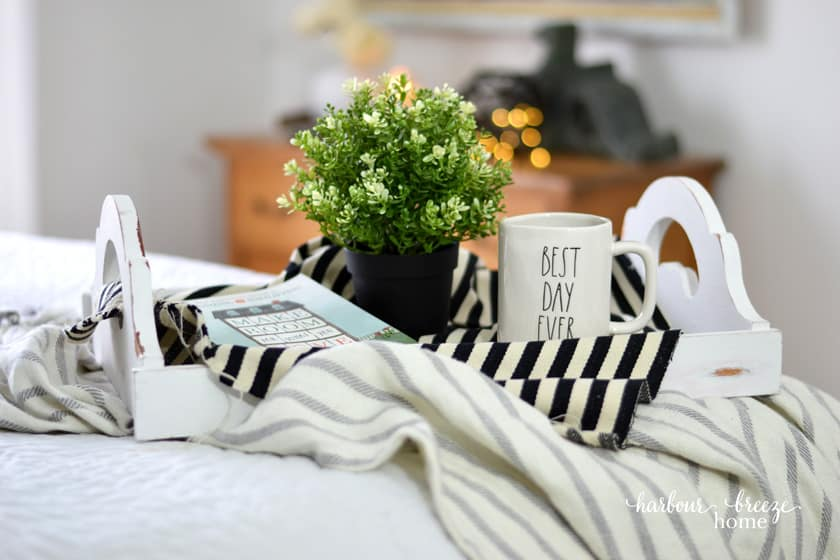 Tray with organization book and coffee on the bed.
