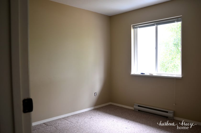 Empty small room with small window before hanging floating shelves.