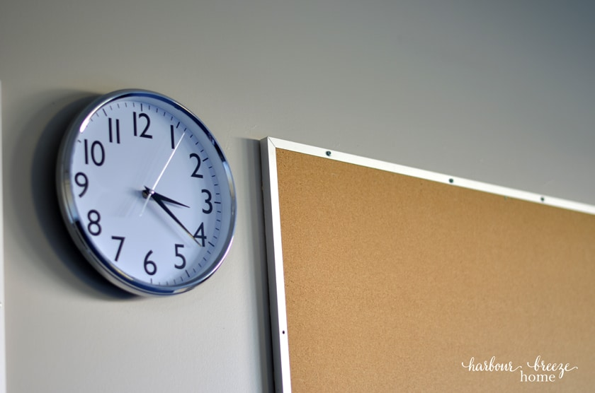 clock beside a bulletin board