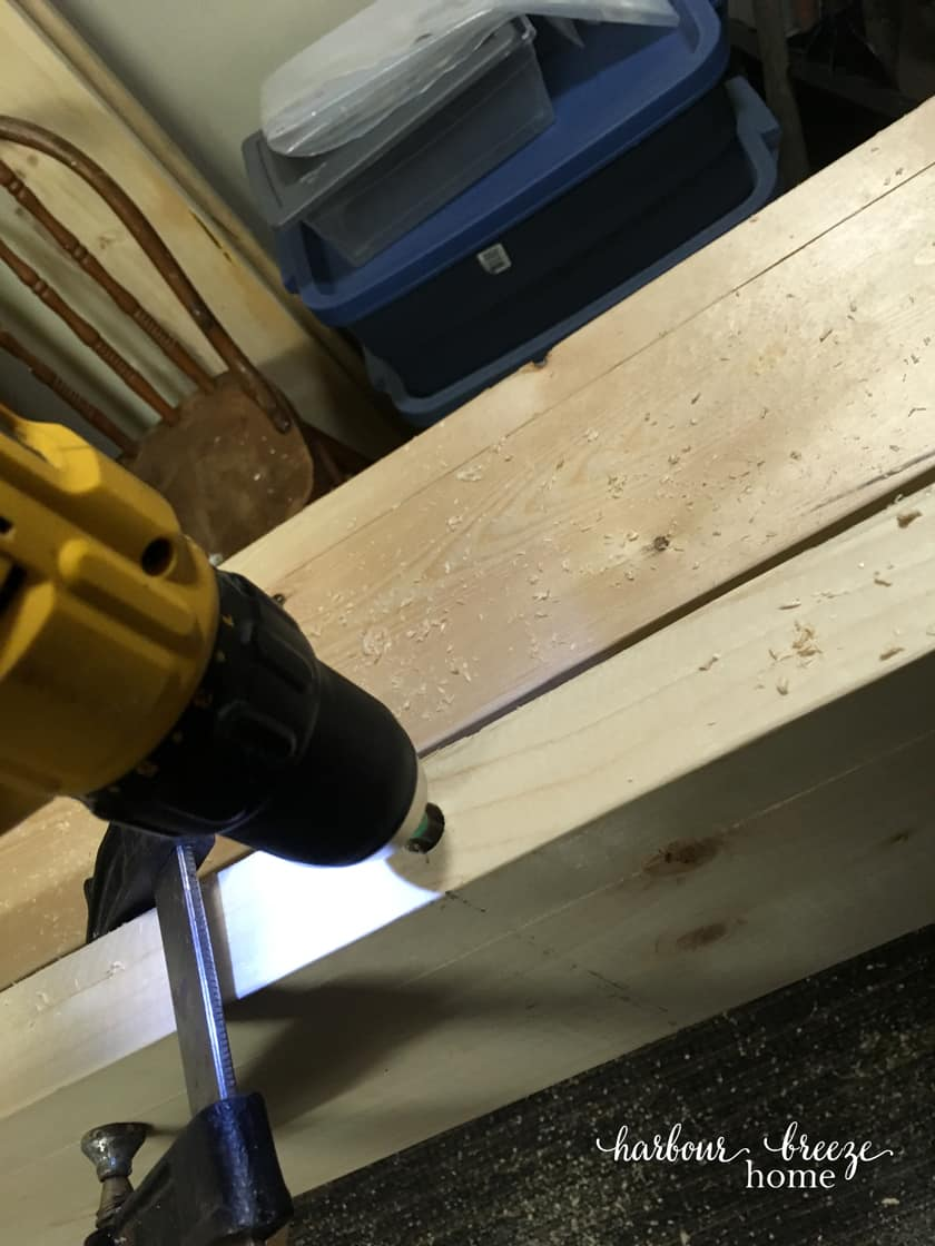 A drill drilling into the DIY floating shelf to make room for the dowel that will be inserted into it.