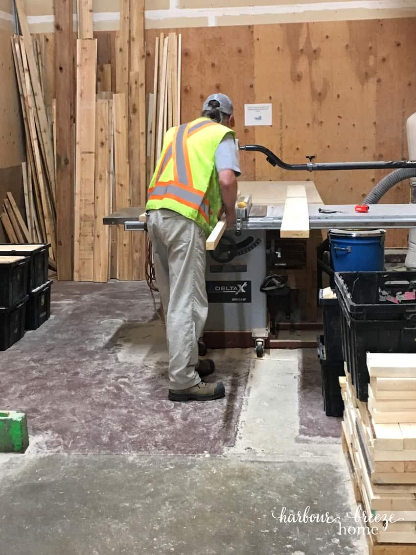 Man cutting boards for DIY floating shelves.