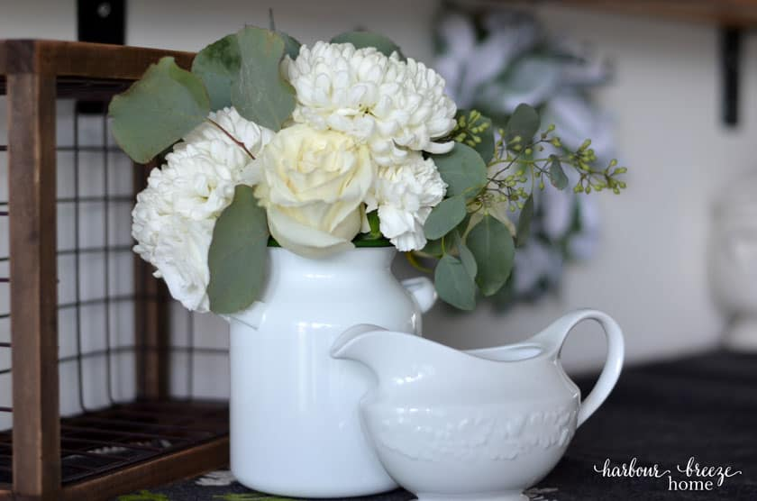 Ideas for decorating wall shelves for winter can include fresh flowers in a white vase.