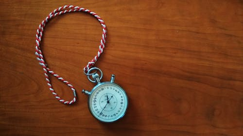 Picture of a stopwatch sitting on a wood surface.