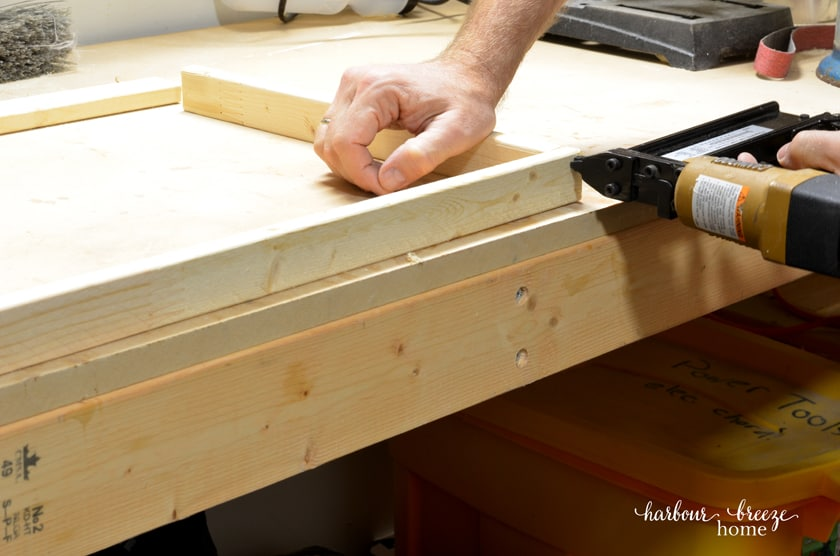 Using a brad nailer to attach the 4 corners of a homemade picture frame together.