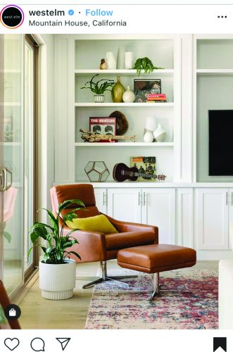 This picture of a white bookcase styled in a modern look with a brown leather chair in front with a large plant from West Elm was the jumping off point for decorating shelves in the living room.