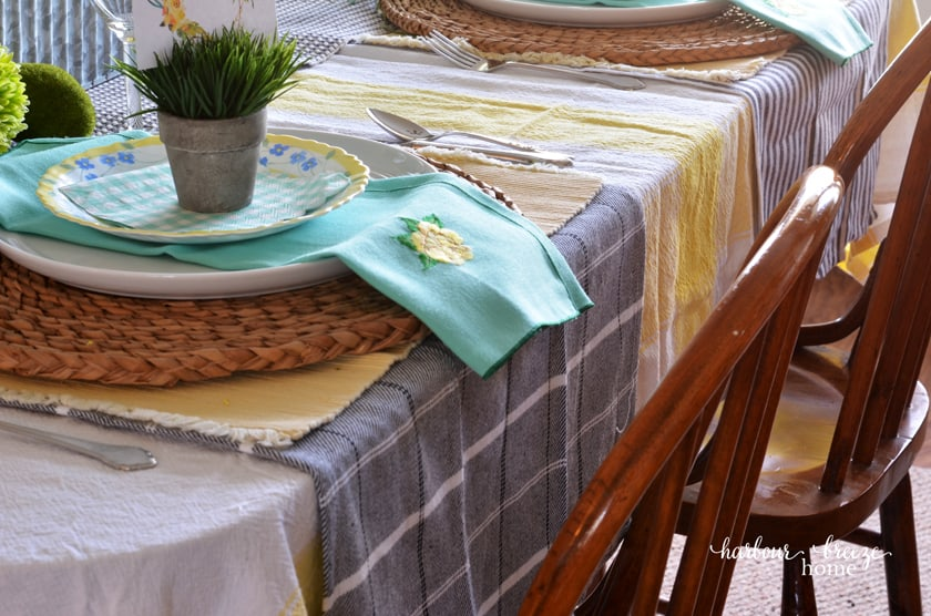 Layer the table with a yellow striped tablecloth, plaid dishtowels under the placesetting, and stacked plates on a woven charger.