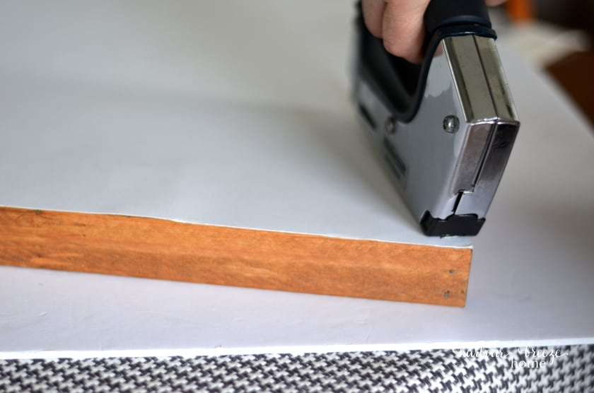 Use a staple gun to attach the art to the finished diy picture frame.
