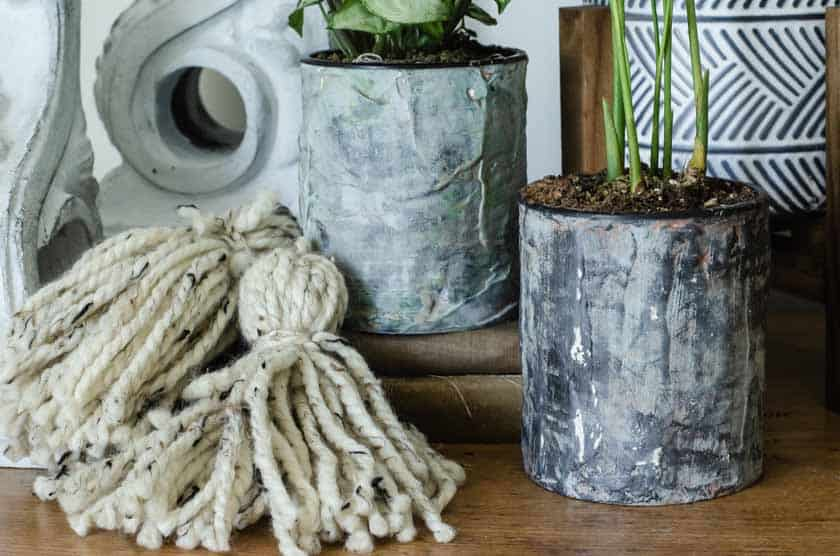 Finished DIY flower pots out of tin cans that look like cement.