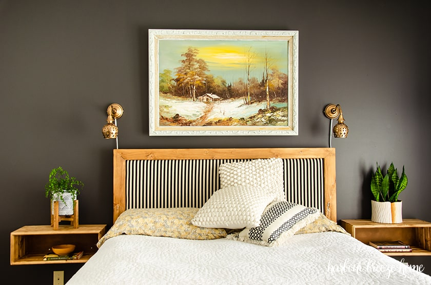 Bedroom wall painted in a dark gray color with a bed and end tables.