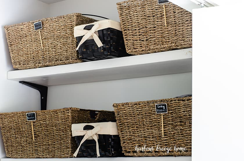 Pretty organization baskets in a closet that has been decluttered.