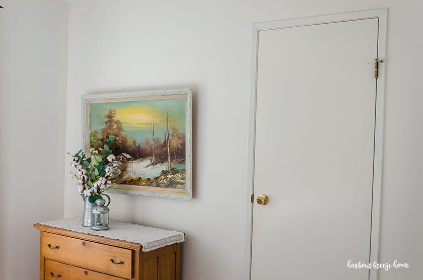 White interior door with thin trim around it and a brass door knob - before new bedroom door knobs
