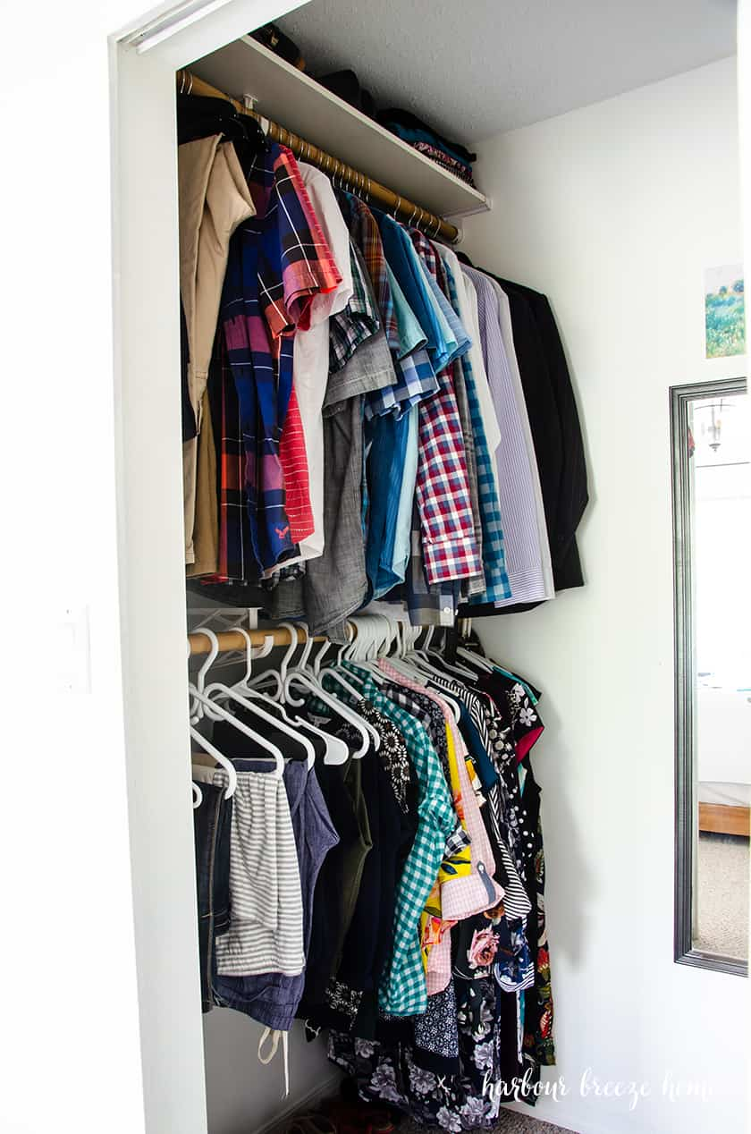 Clothes hanging neatly in a closet.