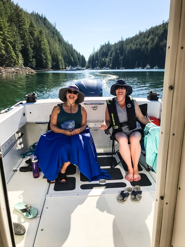 Two women sitting in the back of a boat with bucket hats on.
