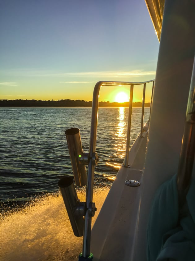 A boat driving into a sunset.