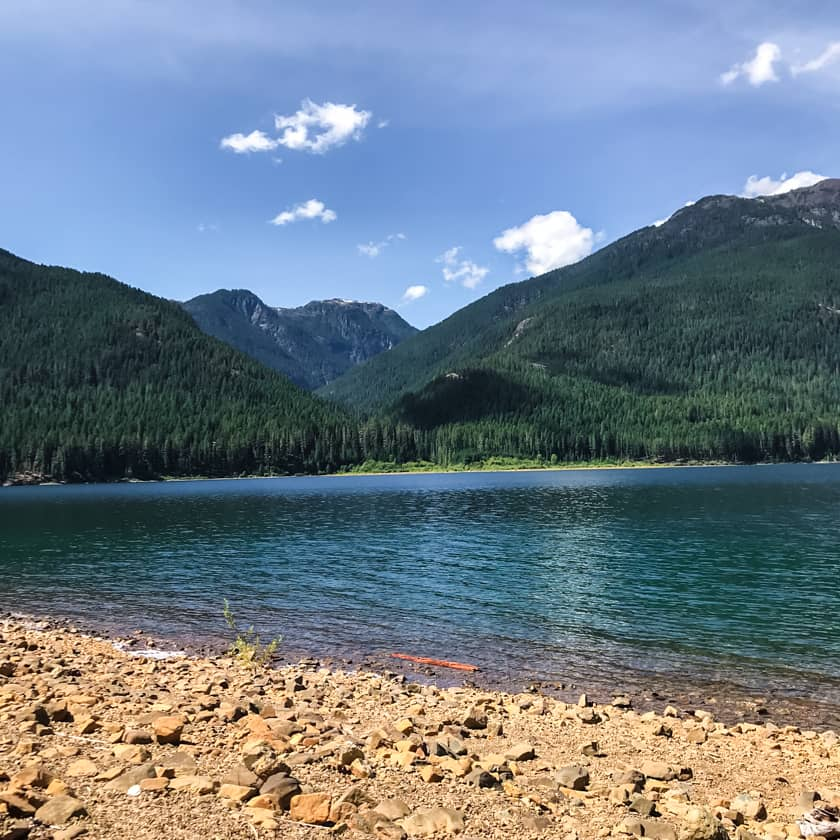The clear blue-green water of Buttle Lake framed by a mountain range.