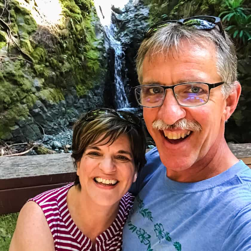 A couple standing in front of a waterfall on Vancouver Island, BC Canada.