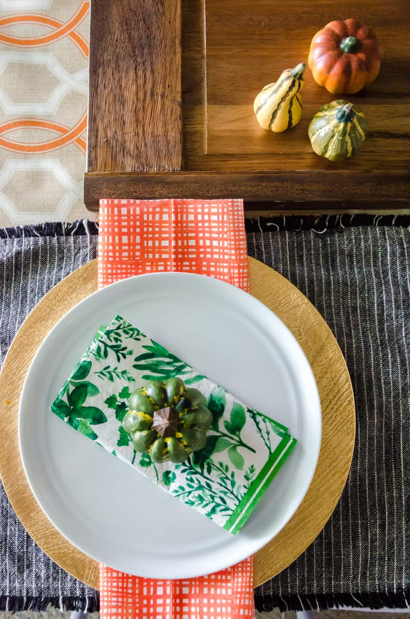 A table setting with a faux pumpkin sitting on top of the plate.