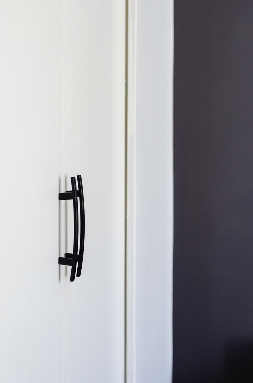 Close up of 2 modern door pulls on bi-fold closet door