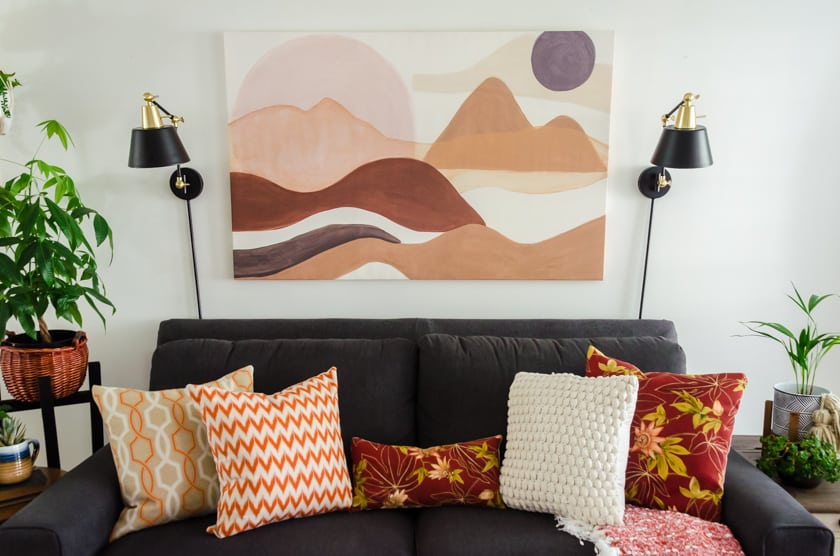 Gray Lazboy couch with boho style landscape art above it.