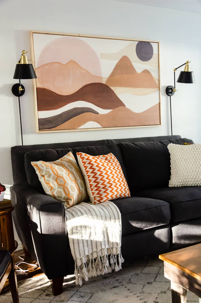 Adding a striped blanket draped on a gray Lazy-boy couch with fall colored throw pillows - an easy room decor idea for Fall!