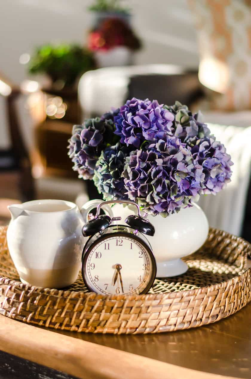 Coffee table decor perfect for Fall with a farmhouse boho look - a vase of flowers, stoneware pitcher, and vintage look clock.