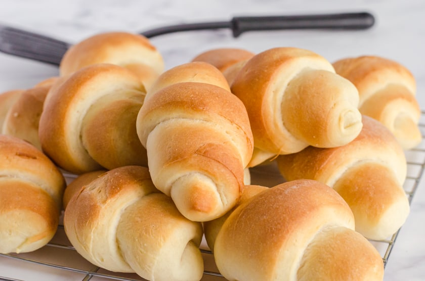 Crescent shaped homemade bread machine dinner rolls piled on a cooling rack.