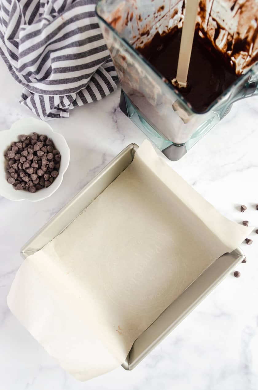 Parchment paper lining a square pan with brownie batter beside it.