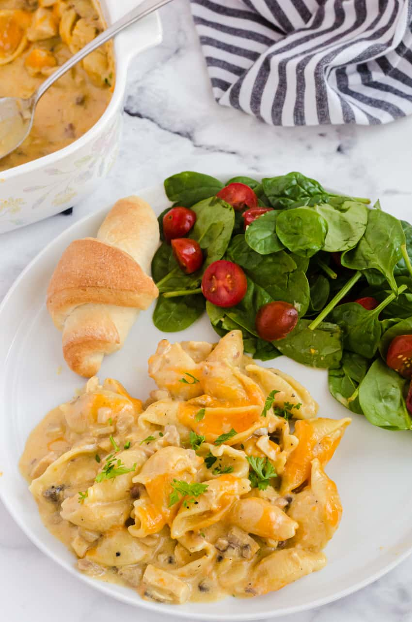 leftover turkey casserole recipe served on a plate with a side salad and dinner bun