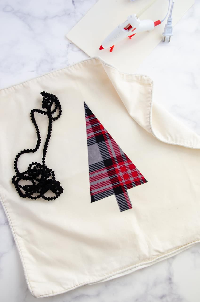 A glue gun can be used to glue on pom pom trim to a DIY Christmas Tree pillow.