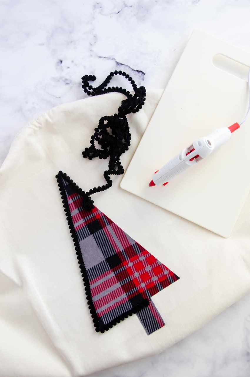Black pom pom trim around a plaid flannel Christmas tree on a white pillow cover is a great farmhouse style DIY Christmas decor project.