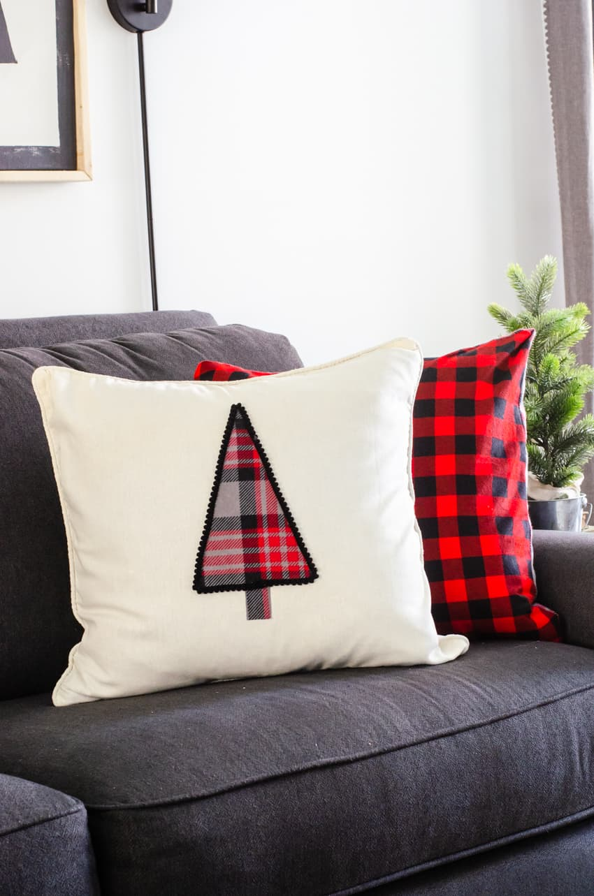 A DIY Christmas tree pillow propped up on a grey couch in front of a red buffalo check flannel pillow.