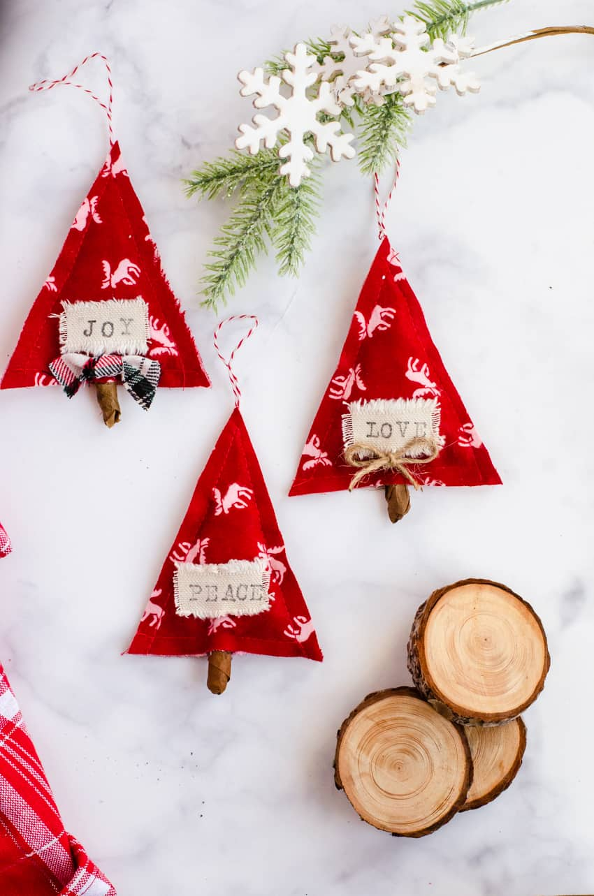"3 Red and White DIY Scandinavian Christmas ornaments made out of fabric and stamped with the words ""joy, love, and peace""."
