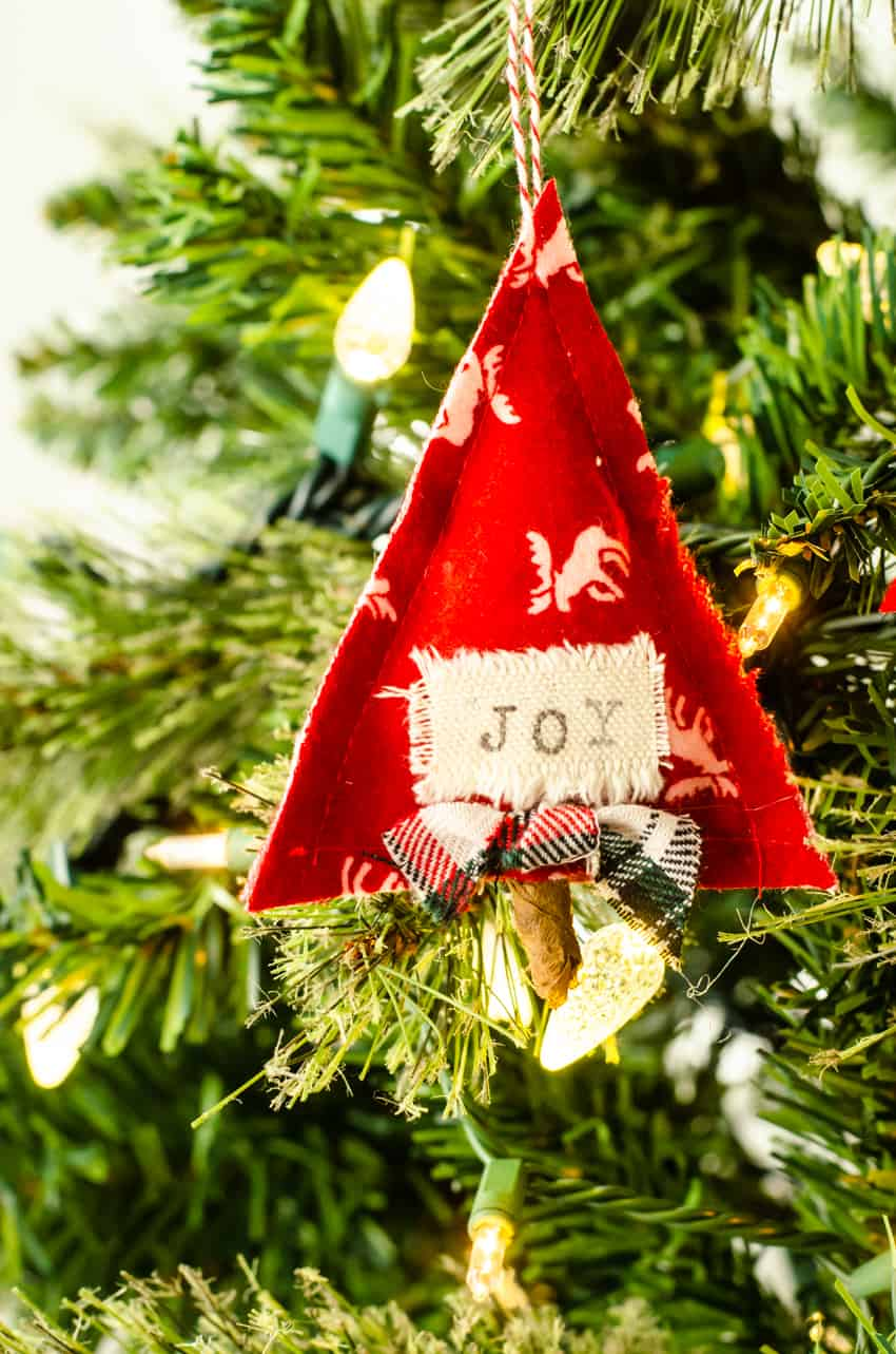 "DIY Scandinavian Christmas Ornament shaped like a tree with the word ""joy"" on it hanging in a tree."