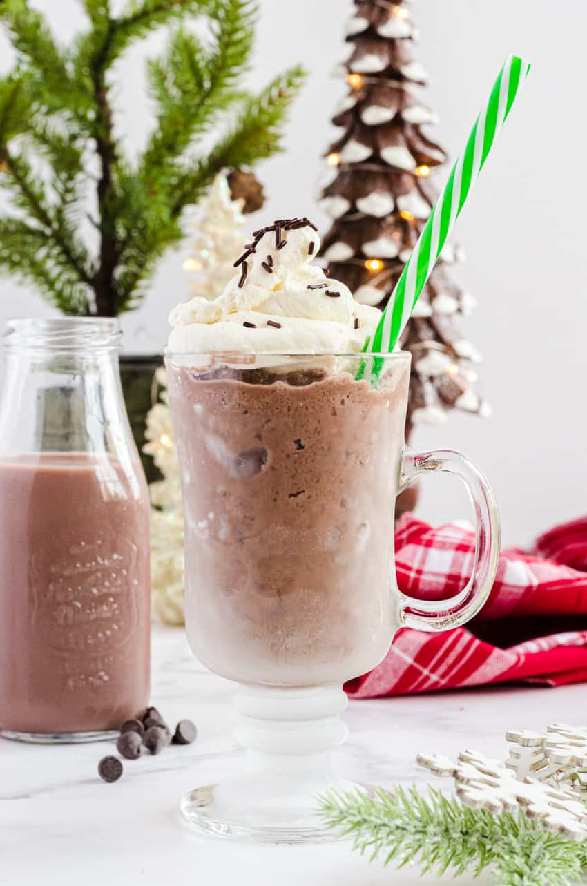 Clear mug with frozen hot chocolate in it with a green striped straw.