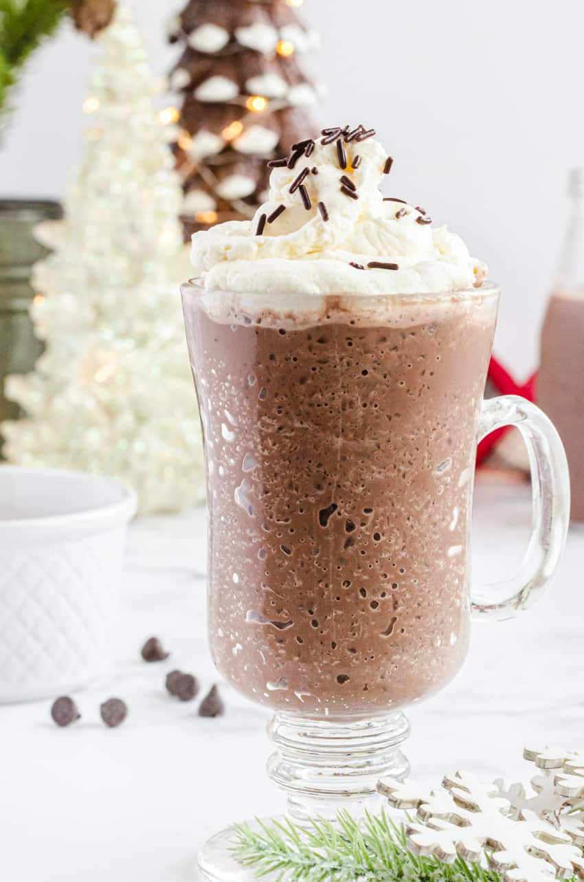 A mug of frozen hot chocolate with Christmas tree lights in the background.