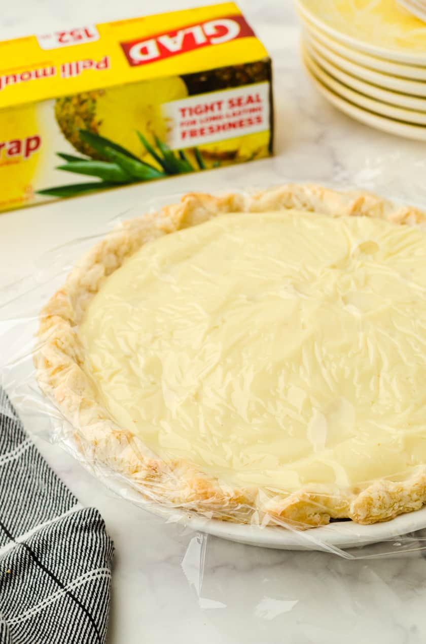 Banana Cream pie with plastic wrap covering it.