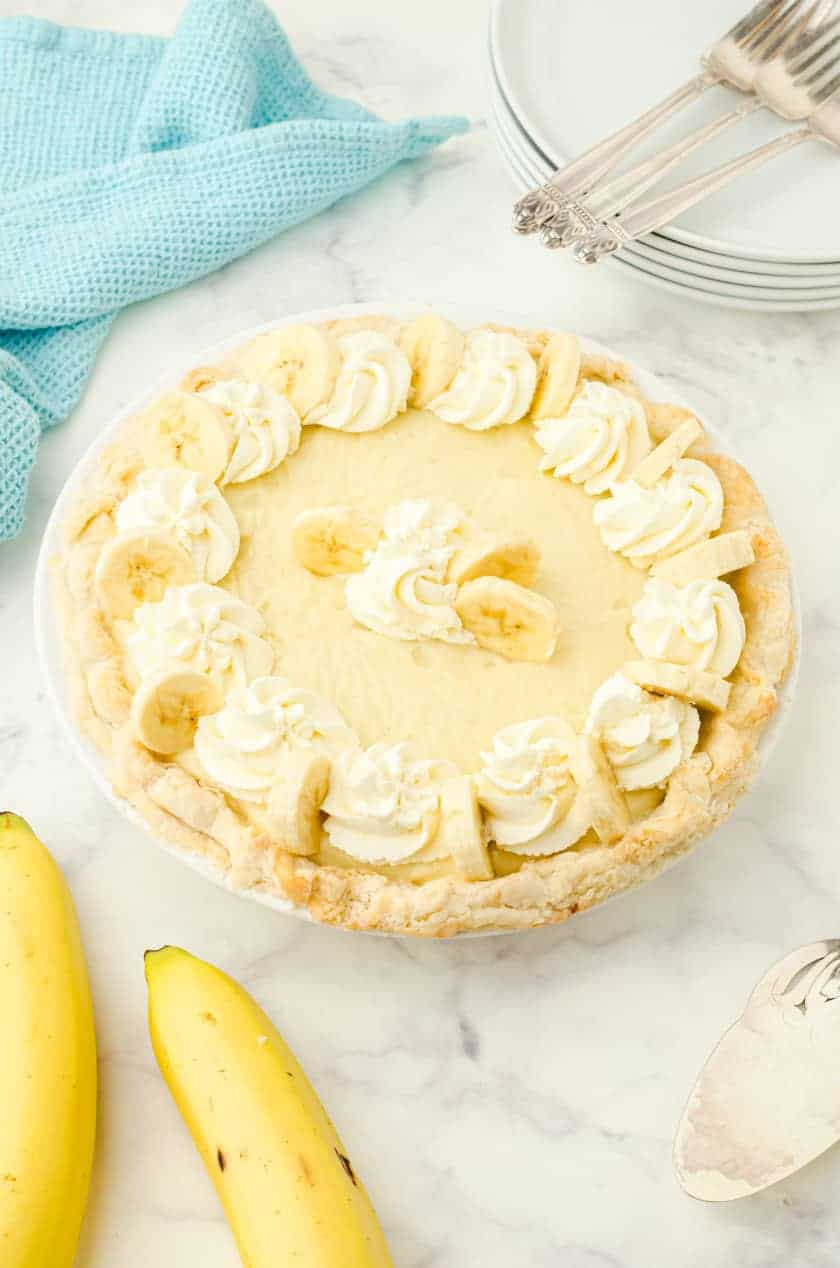 Whole banana cream pie with whipping cream and banana slices on the top