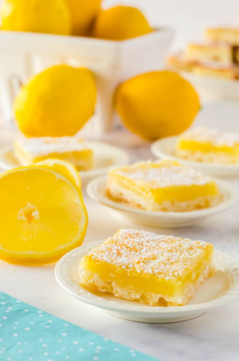 Slices of lemon bars on tiny serving plates.