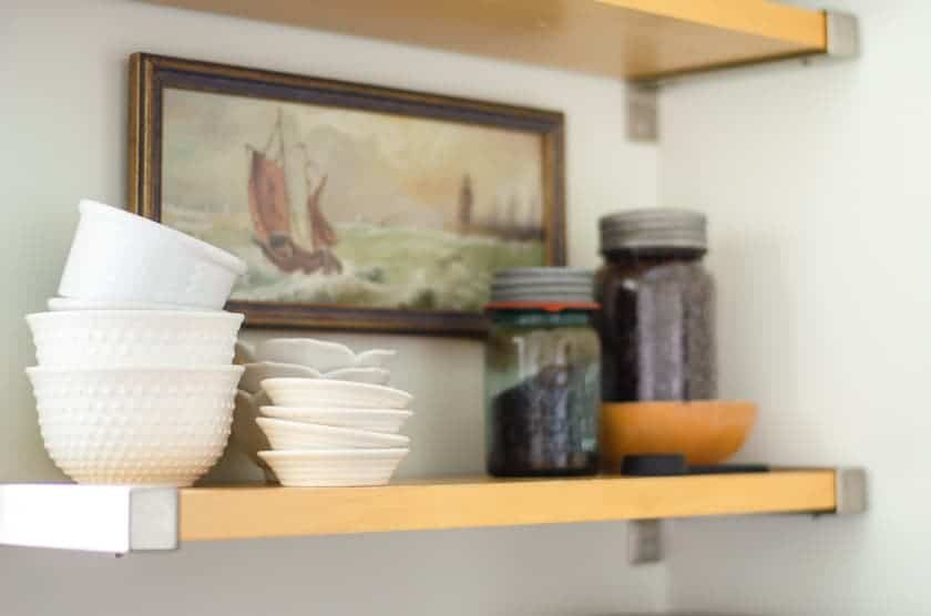 An open shelf with white bowls, antique jars filled with coffee beans, and an old art print of a ship on the wall behind it.