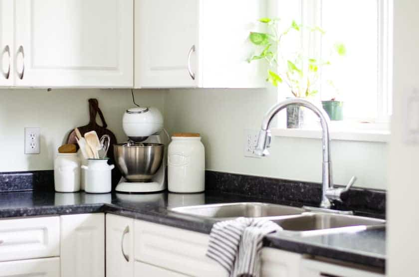 A mixer and canisters sitting on the counter of a small kitchen in the corner beside the sink.