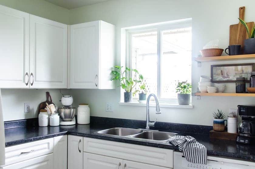 A small kitchen sink with window above and cupboards beside.