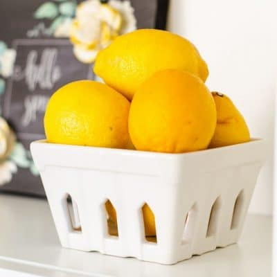yellow lemons in a white ceramic basket bowl