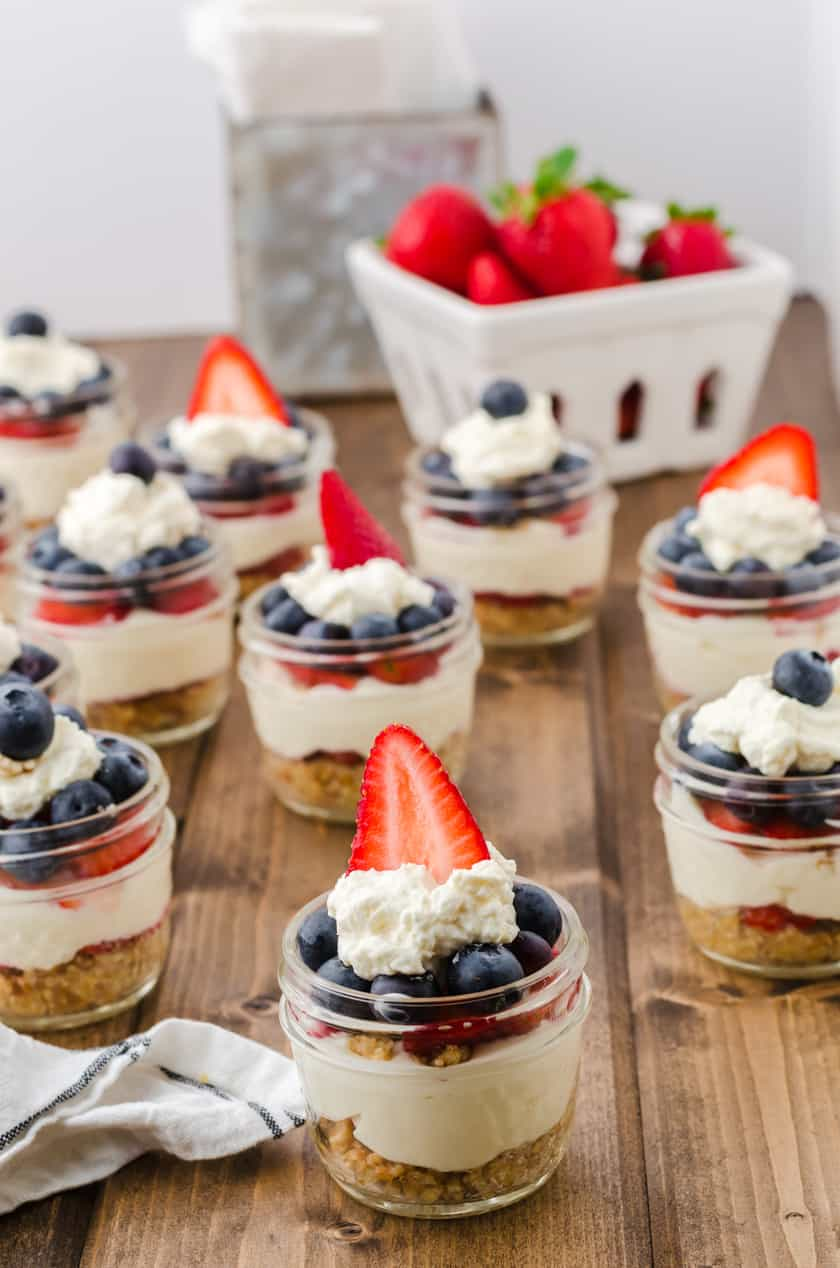 Jars of no bake cheesecake sitting on a wooden table with a basket of strawberries behind.