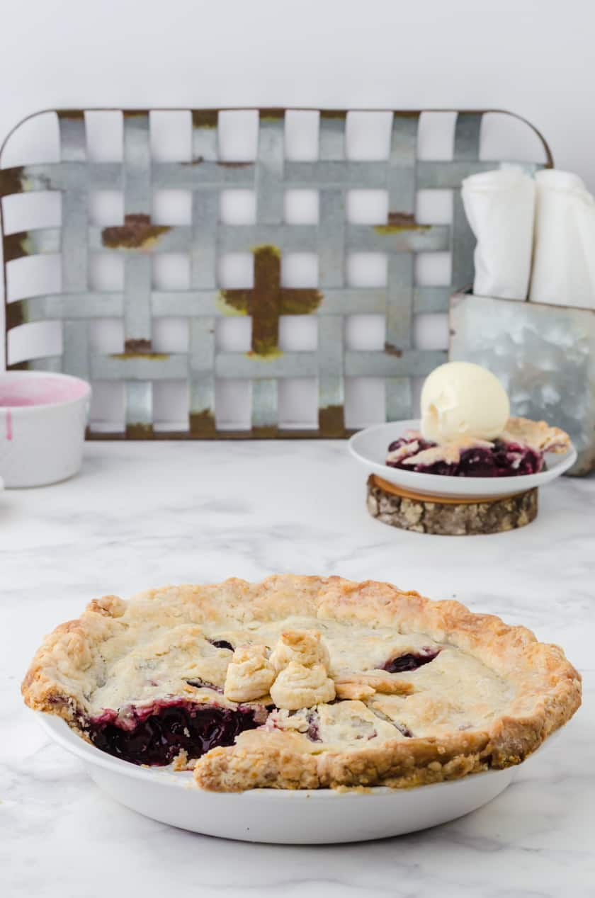 Whole cherry pie with slice out of it.