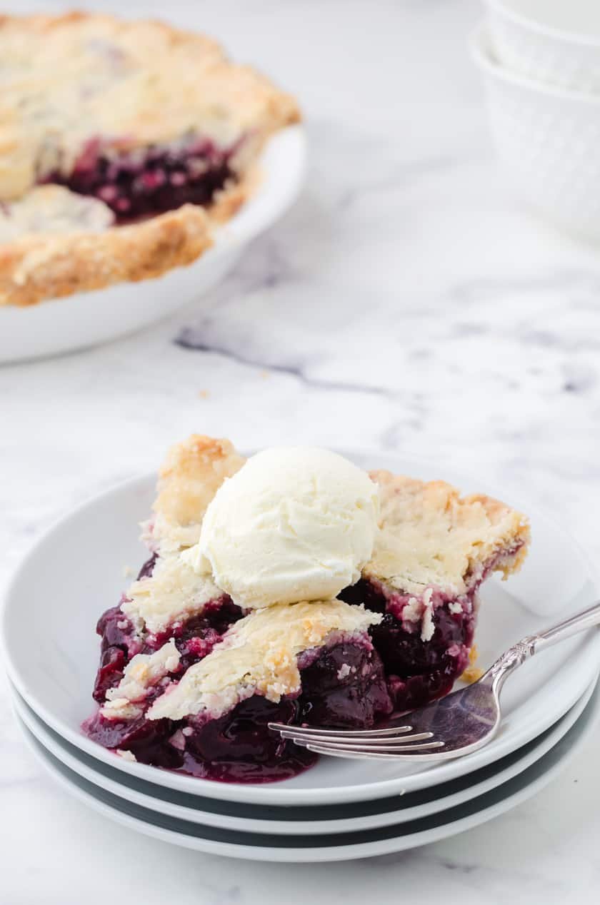 A slice of homemade cherry pie made with canned cherries with a scoop of ice cream on it.