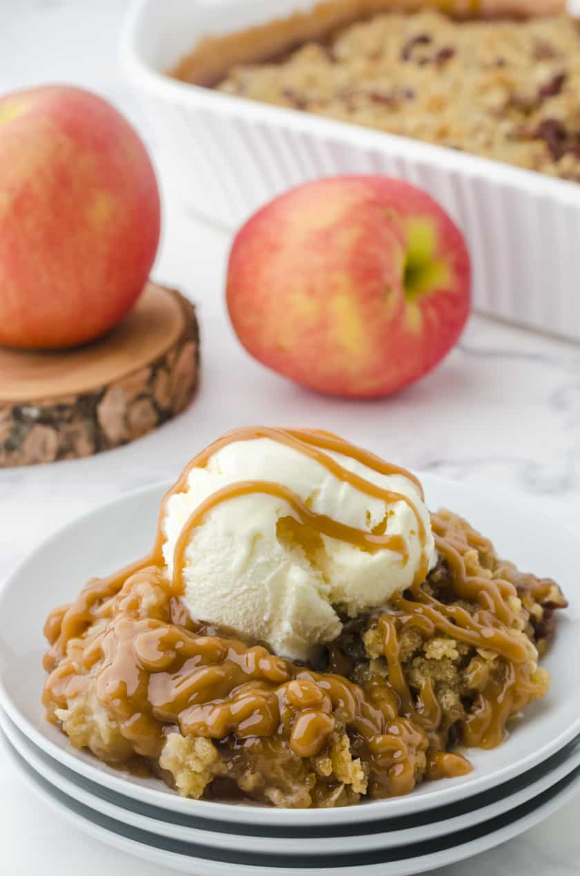 Caramel Apple Crisp dished up with a scoop of ice cream and caramel sauce drizzled over the top.