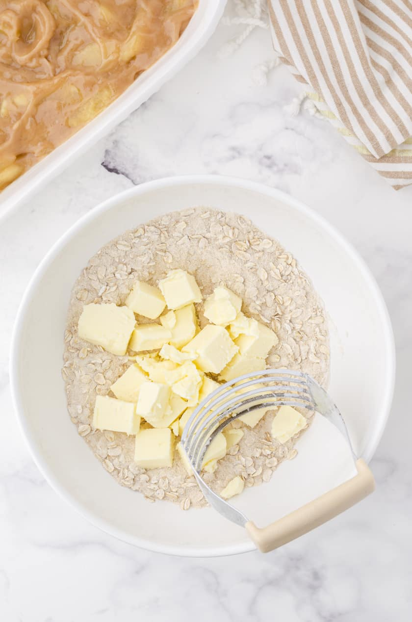 Crisp topping mixture with butter cubes and a pastry blender in a bowl.